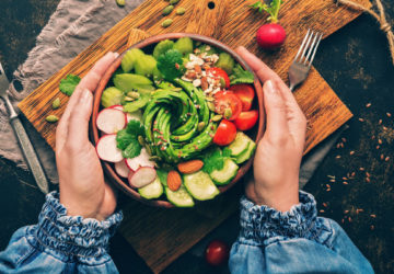 Healthy vegan salad, avocado, celery, cucumber, tomato, radish, nuts and seeds. Girl in denim blouse holding a bowl of vegan salad with visible hands.